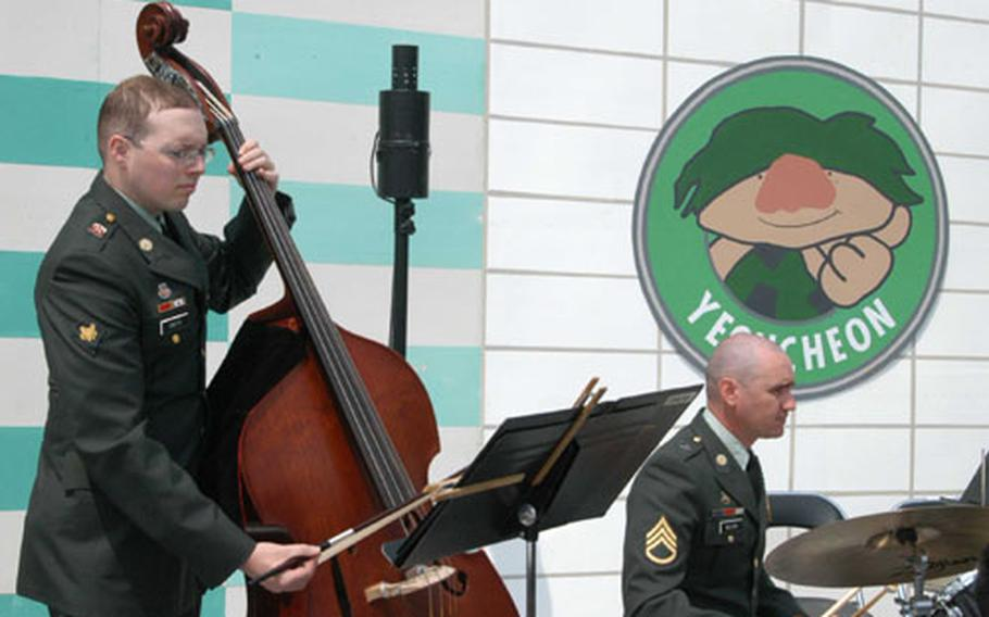 Spc. Chris Smith (string bass) and Senior Sgt. Thomas Wilson (drums) of the 2nd ID Band entertain the crowd at Jeongok-ri.