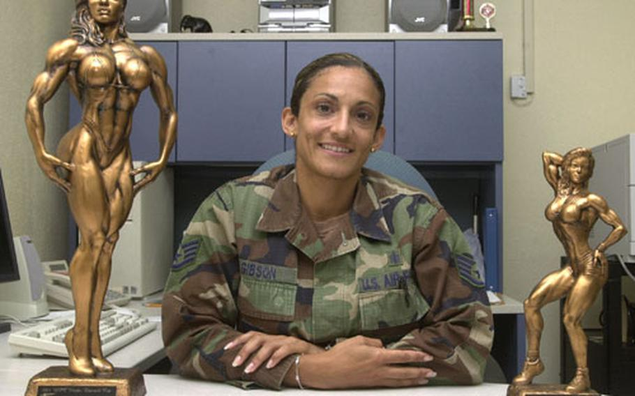 Air Force Staff Sgt. Sabrina Gibson, a mental health technician on Kadena Air Base, sits with the two first-place trophies she recently brought home from the 2004 Weider Emerald Cup Fitness Championship. Gibson took first place in her division and was named overall women's champ. This was her first competition.
