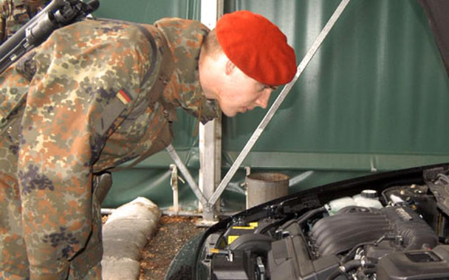 A German army soldier of Panzer Artillerie Batallion 515 from Kellinghusen, Germany, checks under the hood of a car entering Cambrai Fritsch Kaserne in Darmstadt, Germany.