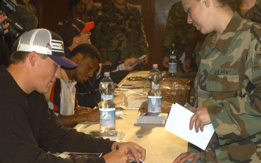 Todd Heap, tight end for the Baltimore Ravens, Warrick Dunn, running back for the Atlanta Falcons, and Keith Brooking, linebacker for the Atlanta Flacons, sign autographs for 1st AD soldiers after talking to them about the experiences in Iraq. The football players said they wanted to thank the troops personally for their sacrifices.