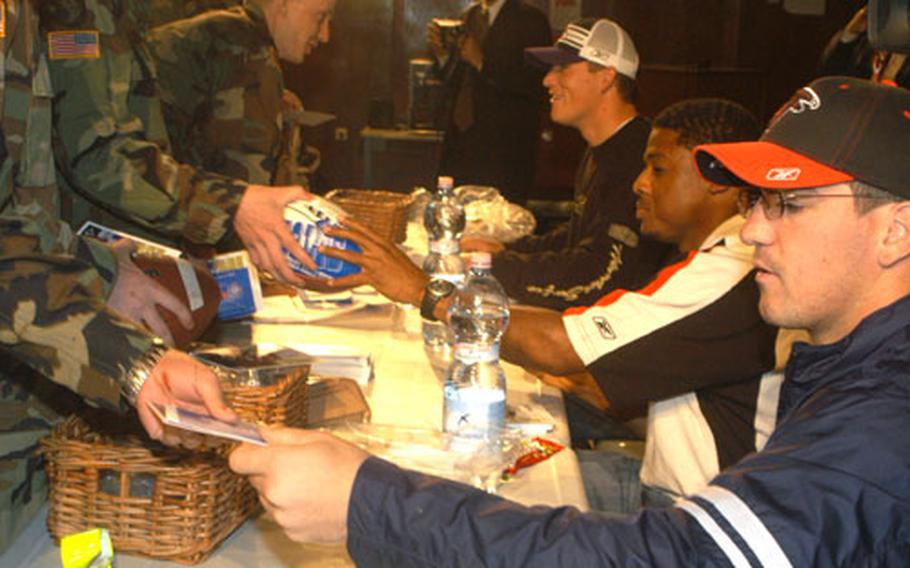 Keith Brooking, linebacker for the Atlanta Falcons, Warrick Dunn, running back for the Falcons, and Todd Heap, tight end for the Baltimore Ravens, sign autographs for troops of the 1st Armored Division who are scheduled to head back to Iraq in the next several weeks after an extension was made on their unit.