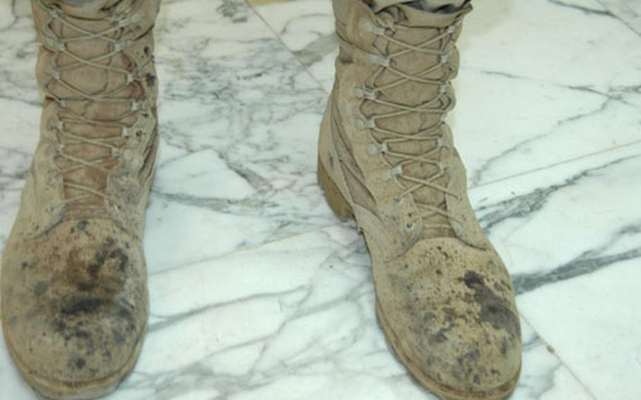 """To get a read of what's happening, """"take a look at people's boots,"""" says the hospital's executive officer, Lt. Col. Steve Smith. These are the boots of Maj. John Hammock, chief of the emergency room."""