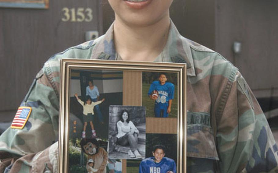 Sgt. 1st Class Viola Millard of Headquarters and Headquarters Company, 38th Infantry Division hold a photos of her four children — Kim, 17, Matthew, 15, Kevin, 14, and Courtney, 10.