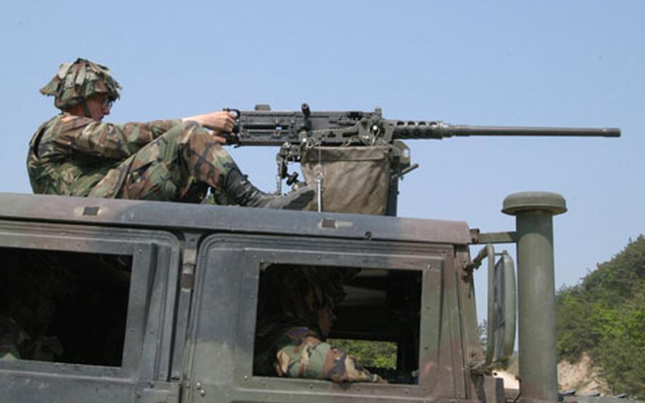 Pfc. Kelly Stewart fires a machinegun atop an HMMWV in Warrior Valley on Thursday.