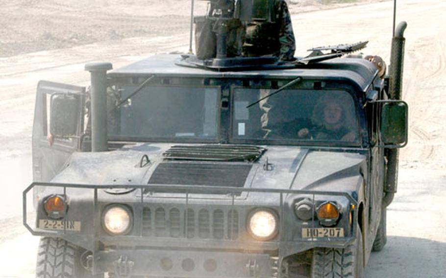 Pfc. Kelly Stewart mans the machinegun atop an HMMWV approaching its firing position in Warrior Valley on Thursday.