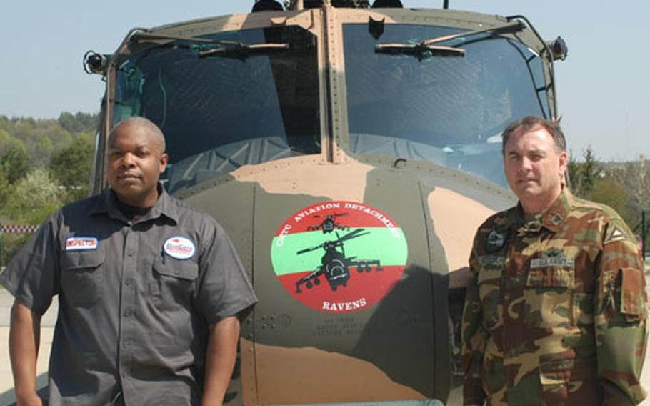 Archie Smith, left, site supervisor for aviation services contractor DynCorp, and Chief Warrant Officer 4 Douglas Hettler, aviation maintenance officer for the Combat Maneuver Training Center Aviation Flight Detachment in Hohenfels, Germany, stand near one of the UH-1 Huey helicopters the unit maintains.