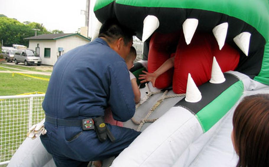 An employee manning the Dragon air toy helped feed the big lizard by helping this little fellow into the fire-breather's big mouth on Saturday in Nimitz Park at Sasebo Naval Base's 2004 Armed Forces Day Sports and Fitness Program.