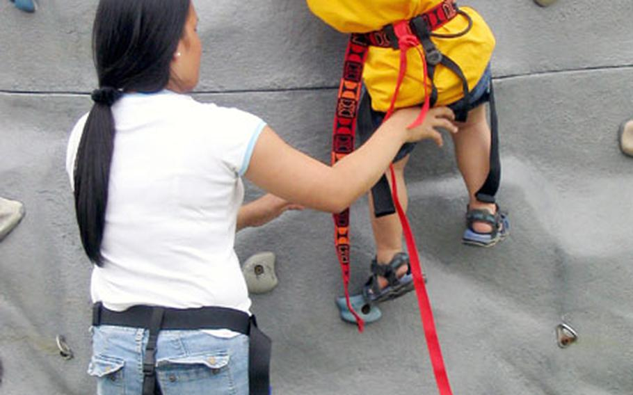 Two-year-old Michael Jones tries his best to get a good start on the rock-climbing wall with help from Michelle Jones, his mother, in Nimitz Park Saturday during the MWR-sponsored 2004 Armed Forces Day Sports and Fitness Program.