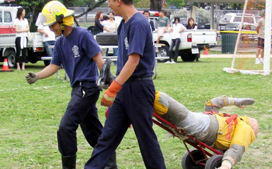 Firefighters from Sasebo Naval Base's Commander Naval Forces Japan Regional Fire Department return a 185-pound fire victim dummy to the starting point for the next competitor during the Combat Firefighting Challenge on Saturday in Nimitz Park during the MWR-sponsored 2004 Armed Forces Day Sports and Fitness Program.
