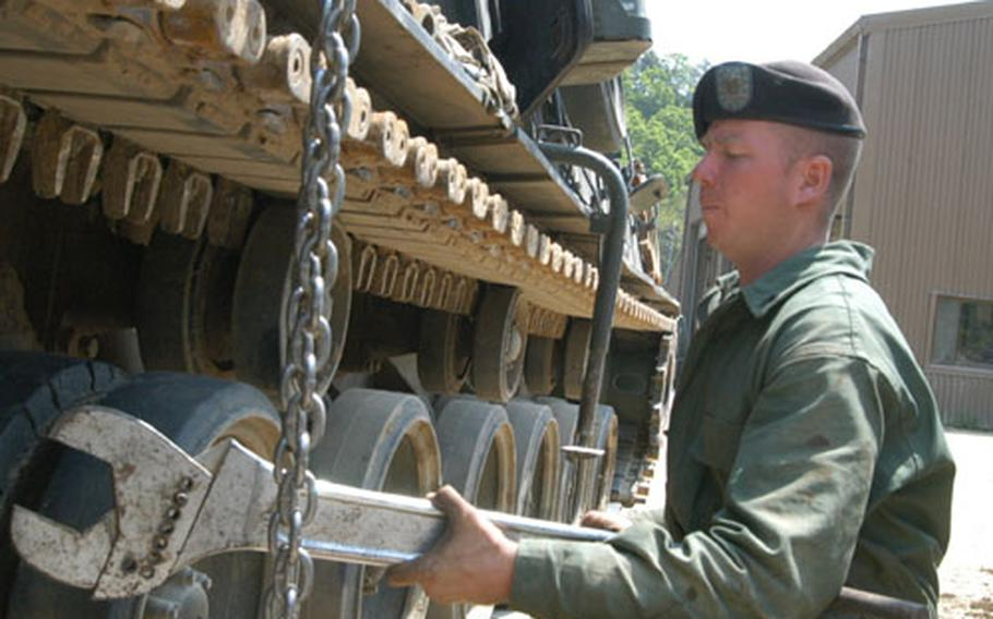 Sgt. Cord McCoy of 2-9 Infantry Regiment's Maintenance Platoon uses a large wrench in an effort to release tension on an M88 track at Rodriguez Range.