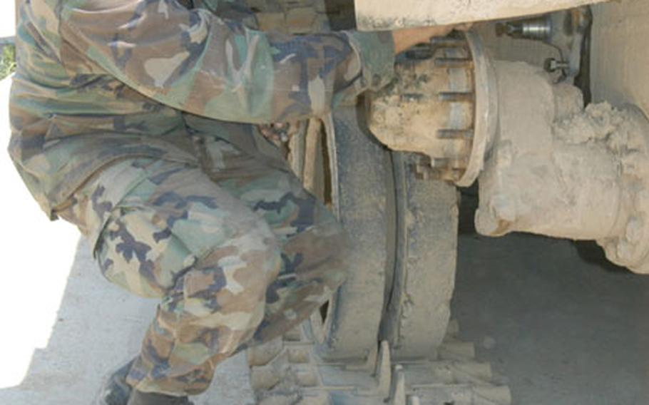 A soldier from 2-9 Infantry Regiment's Mainenance Platoon works on worn out track on a Bradley Fighting Vehicle on Thursday.