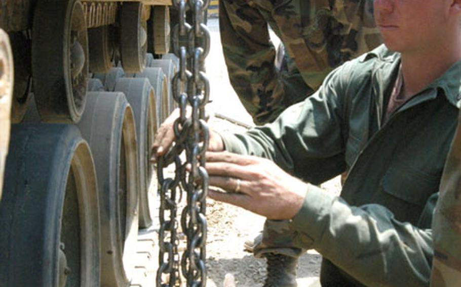 Sgt. Cord McCoy (front), Sgt. Duane Cobb, and Pfc. Ganesh Persaud (drinking water) of 2-9 Infantry Regiment's Maintenance Platoon try to release the tension on an M88 track by undoing a large bolt.