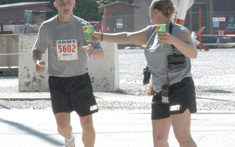A runner grabs a refreshment during Indianapolis Life 500 Mini Marathon satellite race at Eagle Base in Bosnia and Herzegovina. Some 300 runners, mostly National guardsmen, as well as American civilians, Slovenian, Portuguese, Polish, Latvian, Estonian fellow peacekeepers and even members of the Bosnian armed forces took on the 13.1-mile run Saturday.