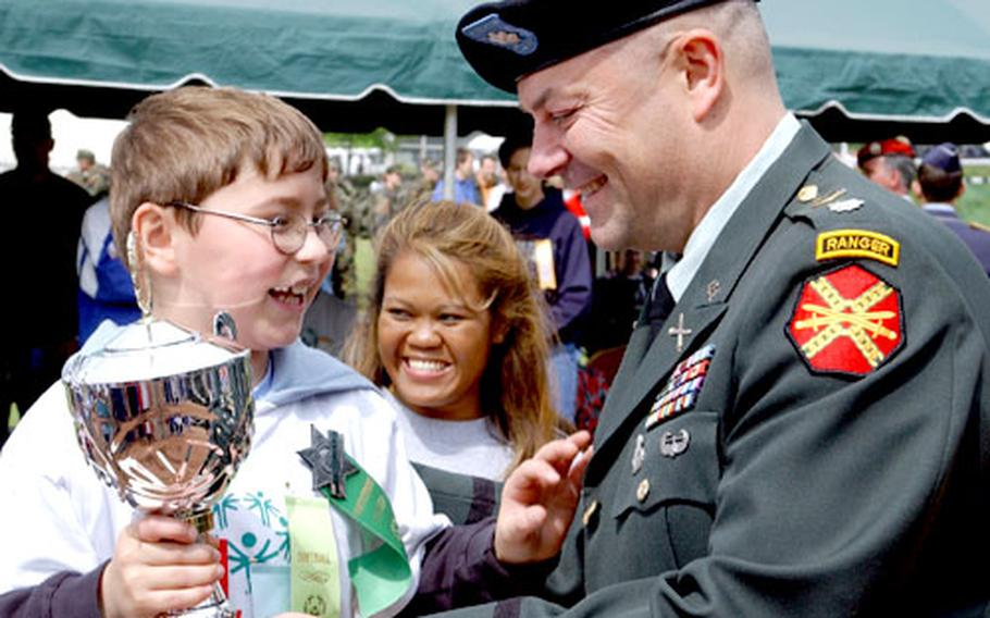 Lt. Col. David Hall, 415th Base Support Battalion commander, presents Wladimir Moser, 8, with the Sarah Bican Inspirational Athlete trophy.