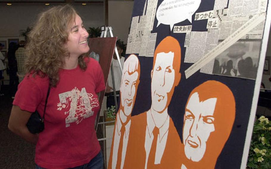Jennifer Abate studies artwork Tuesday night at an exhibit featuring Yokota High School's top artists at Yokota Air Base, Japan.
