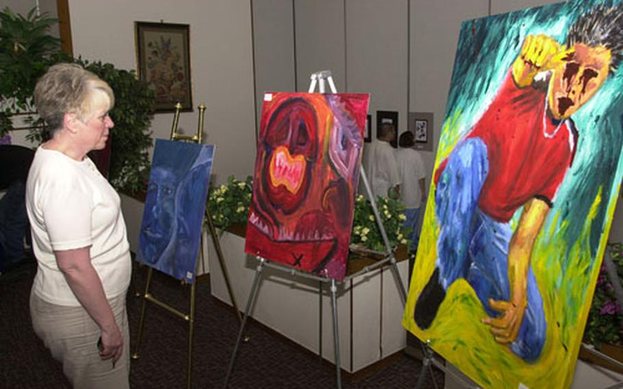 Jan Noyes studies a painting Tuesday night at an exhibit featuring Yokota High School's top artists at Yokota Air Base, Japan. The exhibit was open to the public and seniors Jason Correll, David Hale, Sarah Hannon and Mike Garcia all showed work.