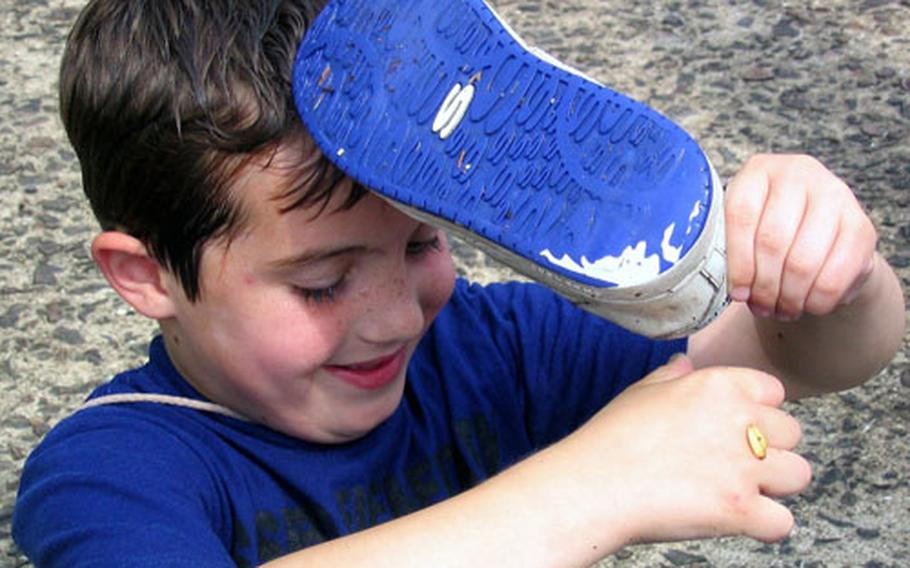 Thomas McGrath, a first grade student at Sasebo Elementary School, had so much fun playing various water games with classmates that he actually had to remove his shoes and wring them out during the Sasebo Naval Base school's 2004 Field Day on Wednesday.
