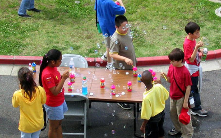 Sasebo Elementary School pupils gather around a makeshift bubble station as their floating creations float through the air Wednesday during the 2004 Field Day at the Sasebo Naval Base school.