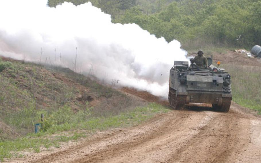 An M-113 lays down smoke to provide cover for 3rd Platoon, B Company, 2-9 Infantry Regiment during an attack in Warrior Valley.
