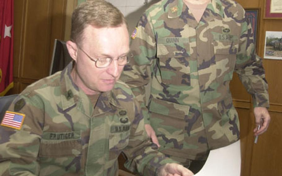 Brig. Gen. Russell Frutiger, (left) the top personnel officer for Army forces in Europe, reviews requests for help from family members of extended 1st Armored Division soldiers with a staff officer.