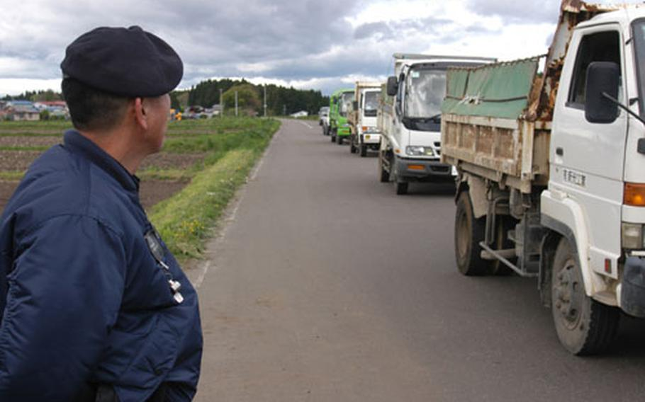 A Japanese national guard watches as delivery trucks head toward the Kamakita Gate at Misawa Air Base, Japan. The gate was opened after Pacific Air Forces mandated that all delivery and construction vehicles, 3/4-ton and heavier, be inspected upon entering Air Force bases in the Pacific.