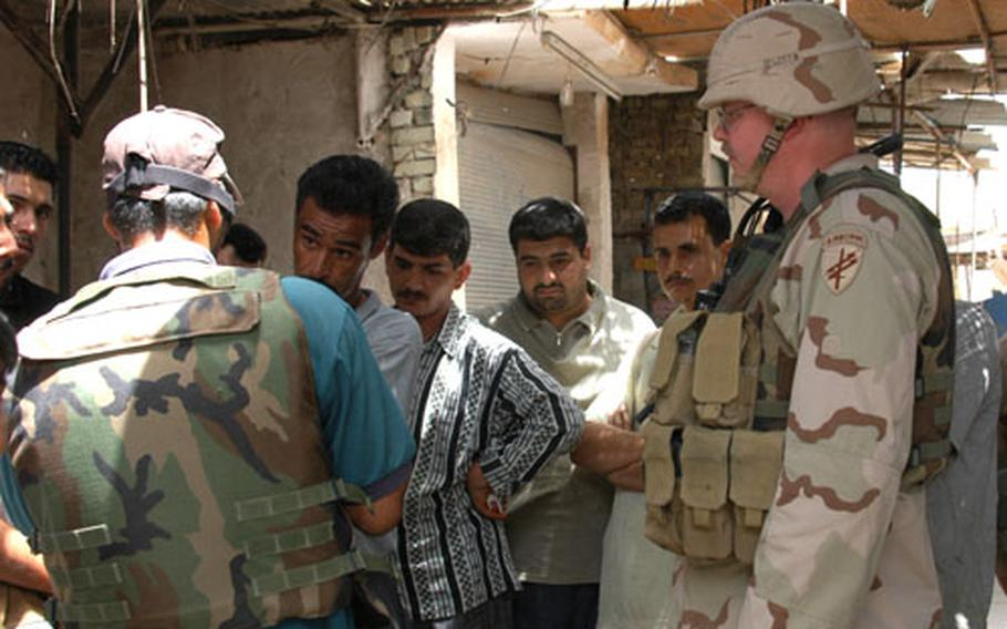 Hussein Ali discusses the need for jobs and electricity with a translator who goes only by Salam, (back to the camera) and Maj. Craig Lester of the 489th Civil Affairs Battalion at a market in south Baghdad.