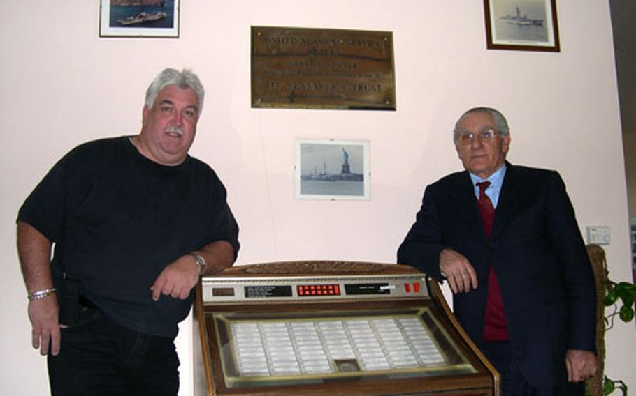 United Seamen's Service Center director Bill Moerler, left, and long-time employee Daniele D'Ettore lean against the center's jukebox in Naples, Italy. The jukebox, like D'Ettore, has been serving center patrons for more than 50 years. D'Ettore, who's done everything at the center from doorman to director in his 53 years of service, said that the jukebox has been with the center for as long as he has. The jukebox has original 45s featuring a wide range of music, from Roy Orbison to Michael Jackson.