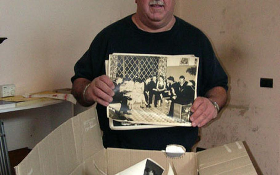 United Seamen's Service Center director Bill Moerler holds some of the hundreds of old photos taken during the center's long history in Naples, Italy. Most don't have any identifying markings or dates, but the large photo he's holding shows sailors from the aircraft carrier USS Coral Sea. The center closed last month after 50-plus years of service.