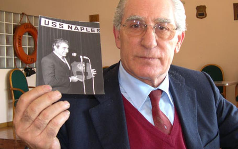 Daniele D'Ettore holds a photo showing him receiving a plaque for the United Seamen's Service Center in Naples, Italy, during his time as director from 1974 until 1982.