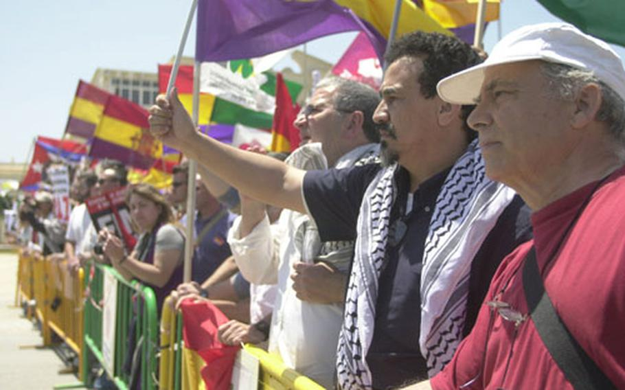 Protesters carry flags and protest the Iraq war on Sunday outside Naval Station Rota in Spain.