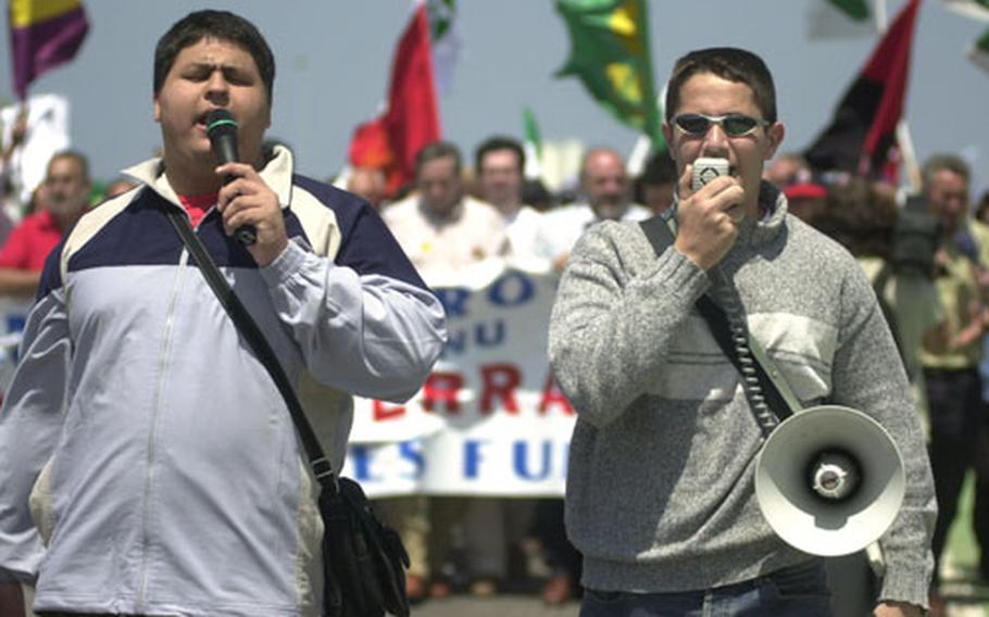A pair of protesters leads the crowd in a series of chants on Sunday outside Naval Station Rota, Spain.