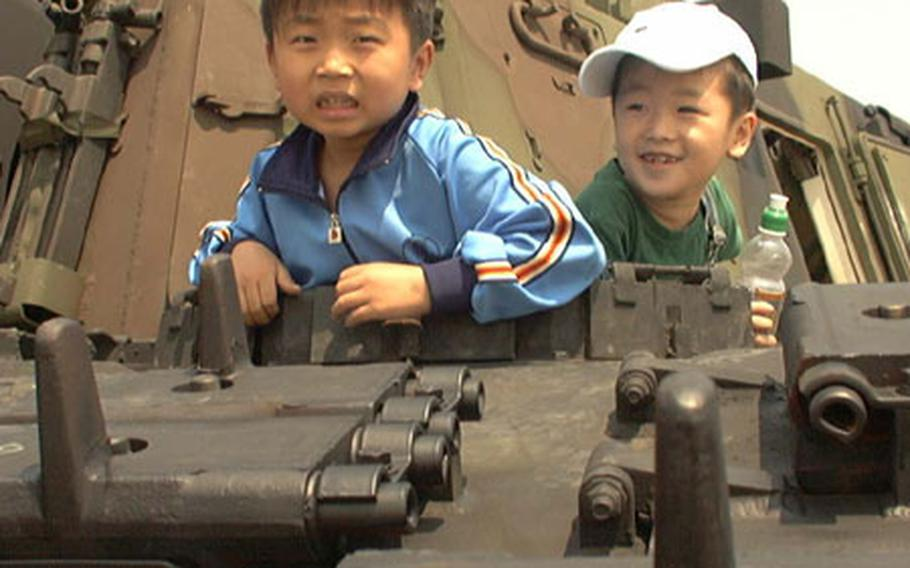At Walker Army Heliport in Taegu, South Korea last May, two boys explore the confines of a U.S. Army M109A6 Paladin self-propelled howitzer during an annual open house at the installation.