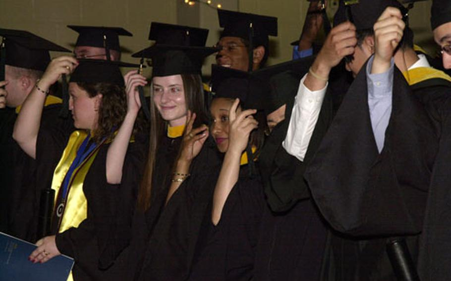 The University of Maryland University College - Korea Class of 2004 switch their tassels to the other side of their mortarboards, symbolizing their graduation Sunday.