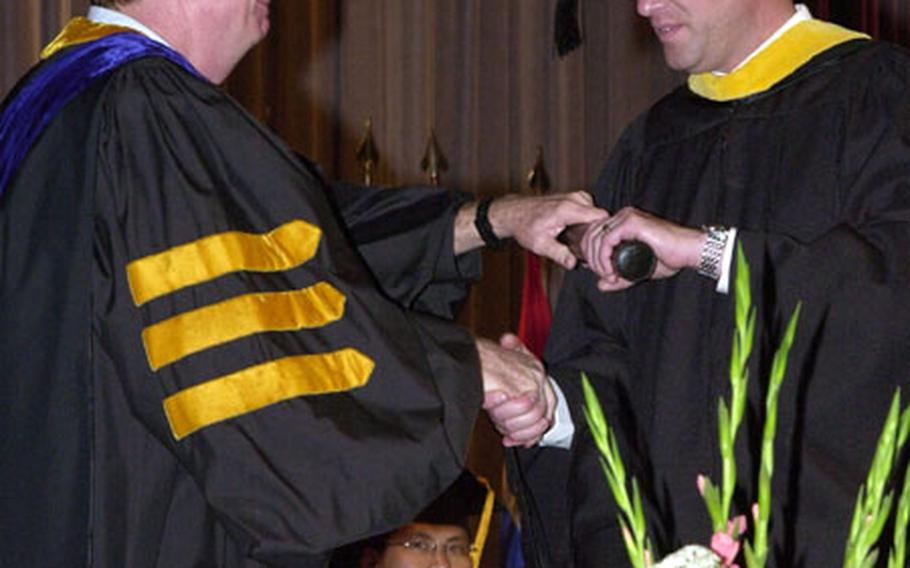 Steven Humes receives his diploma Sunday from Gary Hunt, director of the University of Maryland University College - Korea.