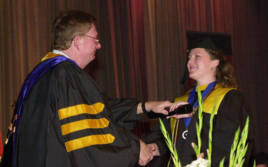 Kristina Broussard receives her diploma Sunday from Gary Hunt, director of University of Maryland University College - Korea.