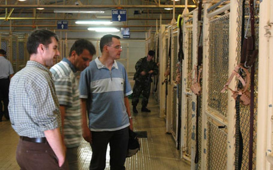 Maj. Darko Semrov, left, Col. Peter Levstek, center, and Maj. Brane Dolenc, three Slovenian army veterinarians, tour the military working-dog kennel at Aviano Air Base, Italy, during a visit Wednesday.