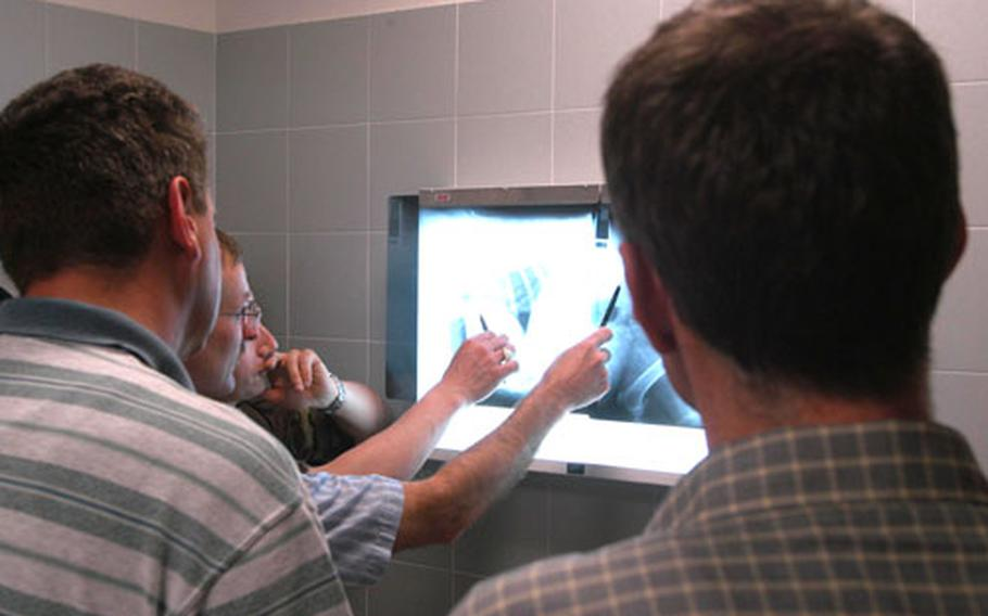 Maj. Tim Settle, deputy commander of the Army's Southern Europe Veterinary Detachment, and Capt. Eric Lombardini discuss X-rays while three fellow veterinarians from the Slovenian army look on during the Slovenians' visit Wednesday to the clinic at Aviano Air Base, Italy.
