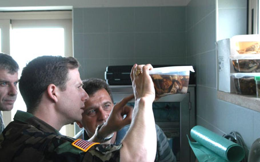 Capt. Eric Lombardini, the Army veterinarian at Aviano Air Base, Italy, shows Slovenian army Col. Peter Levstek, center, a specimen from the clinic Wednesday during a tour of the facility. Slovenian Maj. Darko Semrov looks on.