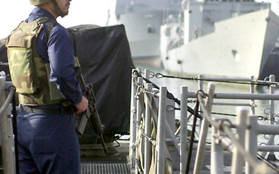 A sailor stands guard aboard the USS Typhoon.