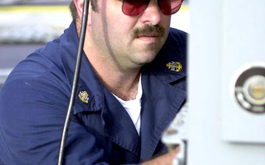 Navy Chief Petty Officer Greg Tillery of Jackson County, Ky., prepares a Mark 38 25mm machine gun aboard the USS Typhoon.