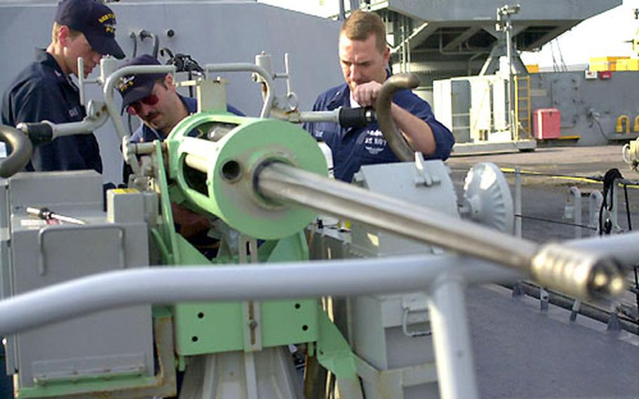 Navy Petty Officer 2nd Class Chad Glover, Chief Petty Officer Greg Tillery and Petty Officer 1st Class Christopher Cooke prepare a Mark 38 25mm machine gun aboard the USS Typhoon at Naval Station Rota, Spain, on Friday. Patrol boats USS Typhoon and USS Sirocco stopped in Rota on their way to the Persian Gulf.