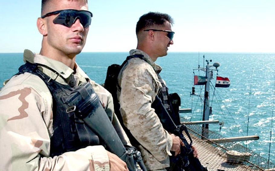 Lance Cpl. Christopher Kotulski and Cpl. Paul O'Donnell stand watch on the flight deck of the Al Basrah Oil Terminal.