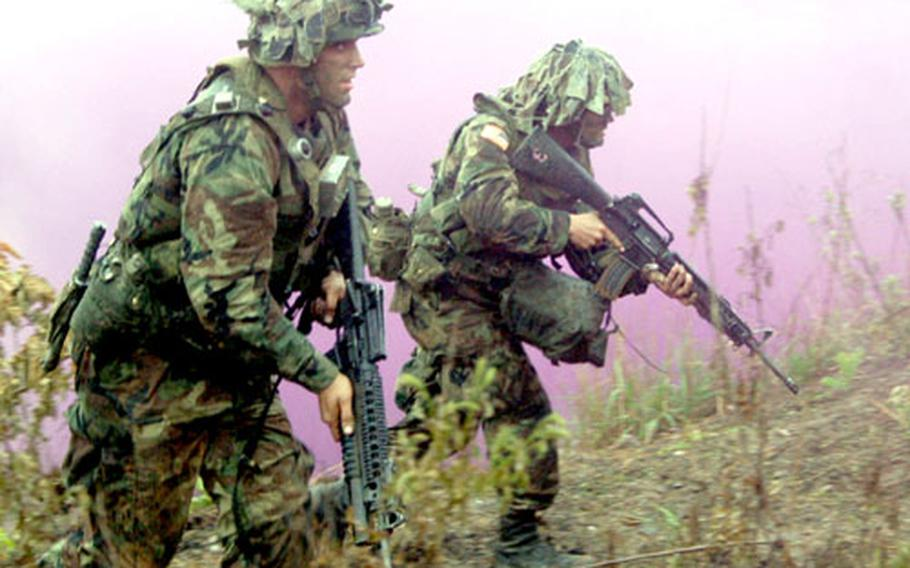 Soldiers from D Company, 2nd Battalion, 9th Infantry Regiment storm up a hillside to take Objective Niner on Rodriguez Range.
