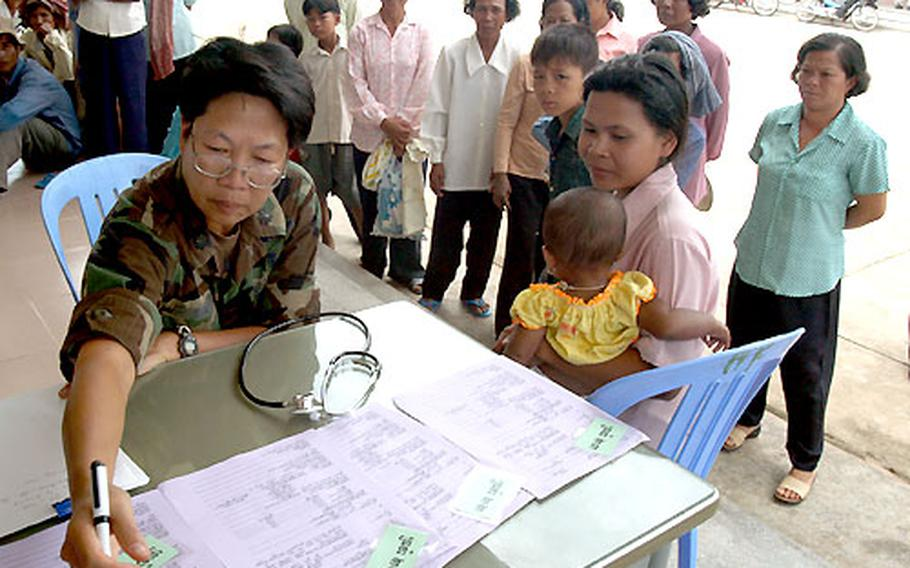 U.S. Air Force Lt. Col. Diep Duong — a nurse normally assigned to Det. 2, 13th Air Force International Health Specialist Program at Hickam AFB, Hawaii — looks over a patient's screening paperwork as she assesses possible patients in a hospital compound in Kep.