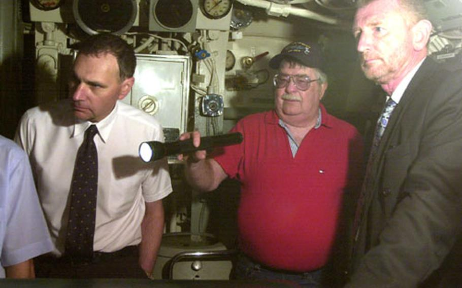Max Bassett, 68, a retired Navy master chief, uses a flashlight as he gives a tour of the World War II-era submarine USS Razorback on Tuesday in Gibraltar.