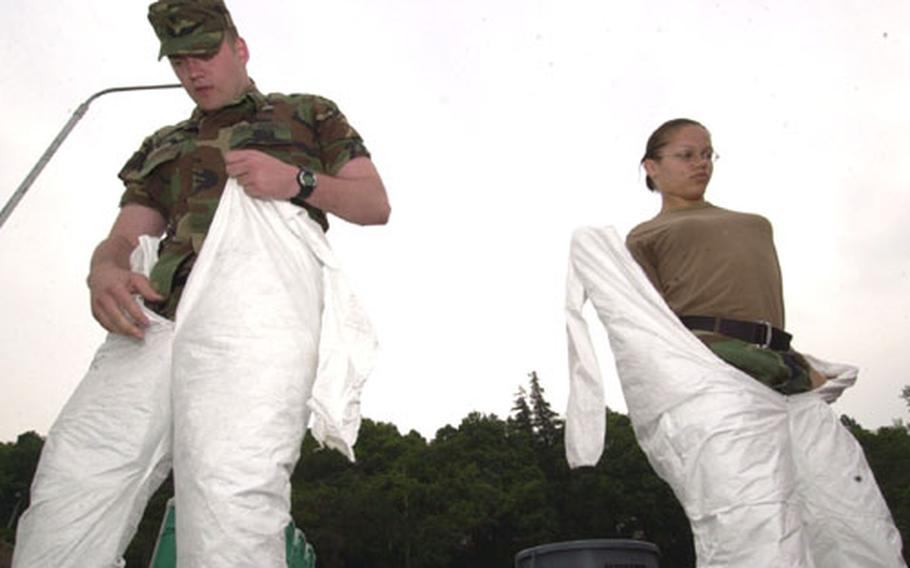 Decontamination members, Spc. Sky Laron, left, and Spc. Jamie Moore, from U.S. Army Japan, get dressed in chemical protective suits at the start of a Chemical, Biological, Radiological, Nuclear and High Explosive Situational Exercise at Camp Zama on Wednesday.