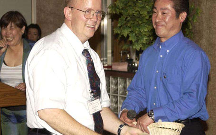 John Niemeyer, CNFJ political advisor, wins a raffle prize at the 7th annual CNFJ Regional Fire Department friendship dinner at the Yokosuka Naval Base Officer's Club.