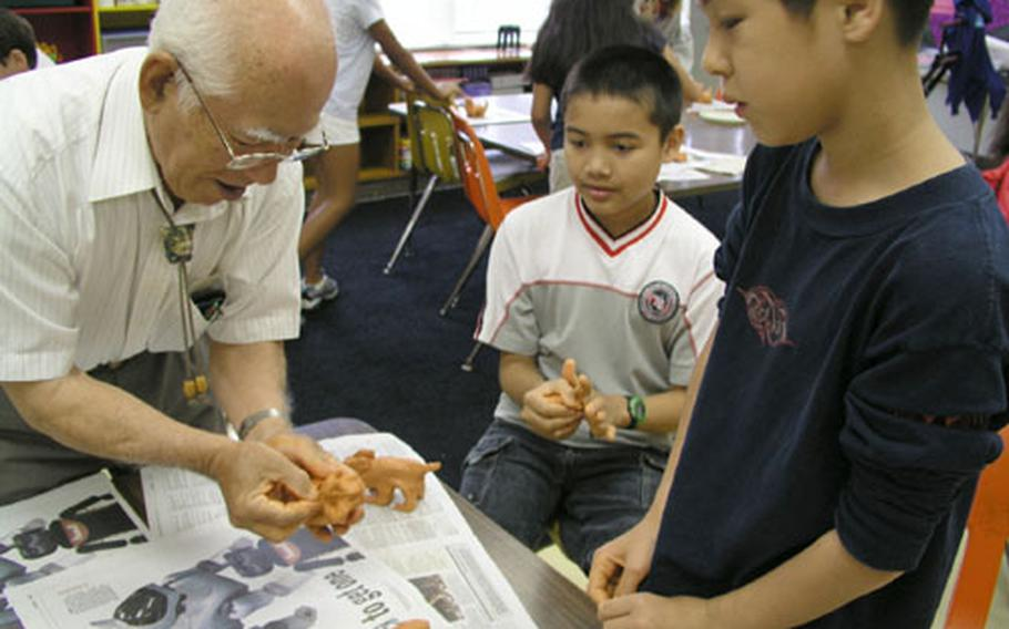 Alex Reid, left, and Stephen Shampine, 5th graders at Stearley Heights Elementary School, watch Mitsuyoshi Ikei show them how to put a final touch on their clay Wednesday during a special art class. Students at the elementary school participated in Shi-Shi making, an event the school celebrates for Asia Pacific Heritage Month.
