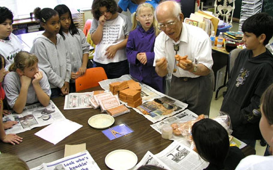 Sculptor Mitsuyoshi Ikei shows fourth graders at Stearley Heights Elementary School how to form a Shi-Shi dog out of clay. During a special art class Wednesday, students at the elementary school on Kadena Air Base enjoyed making their own traditional Okinawa guardian dogs.