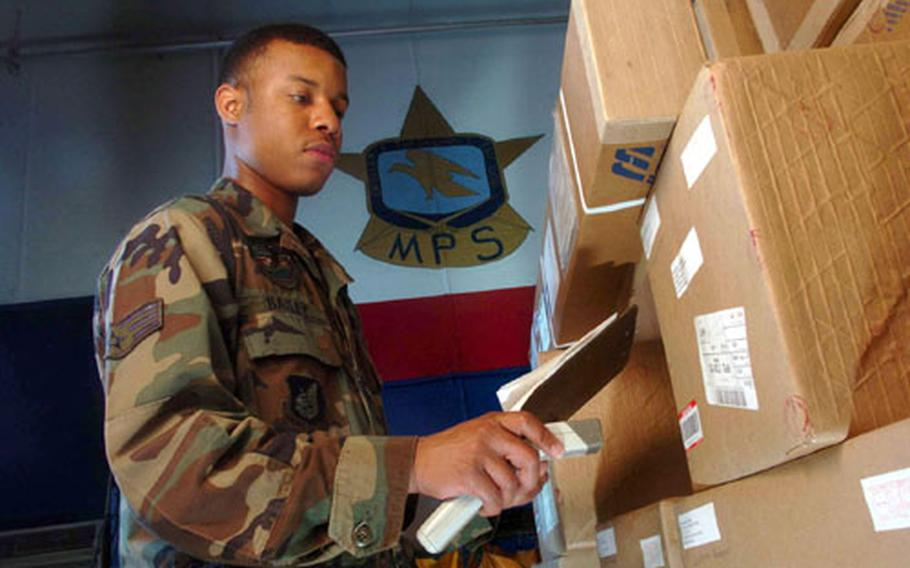 Senior Airman Stacey Bailey from Detachment 2, Air Postal Squadron at Yokota Air Base, Japan, uses a scanner to track registered mail at the mail processing facility here.